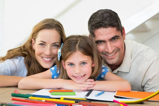 Portrait of loving family with book and crayons sitting at table