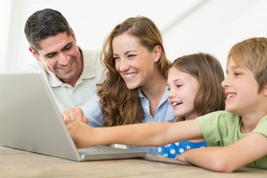 Smiling family of four using laptop at home