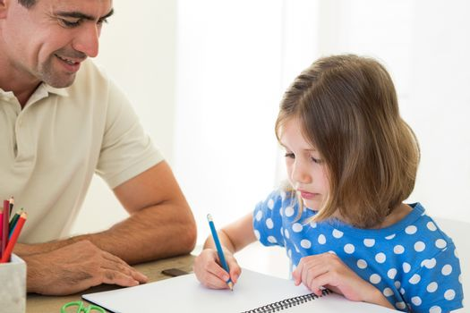 Father looking at daughter coloring