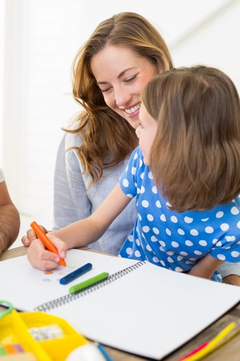 Mother with daughter coloring at home