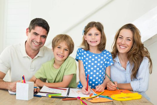 Portrait of happy family drawing together at table