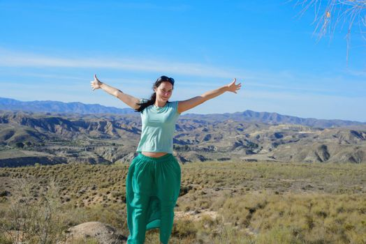 Young happy woman open arms stand at mountain
