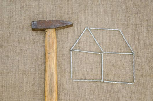 work hammer and outbuilding shape of metallic nail on linen texture background