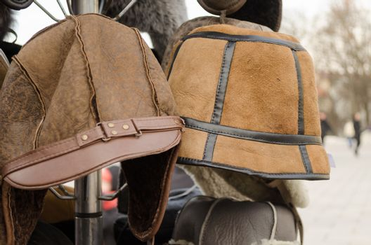 male brown decorated winter hats on rack outdoor