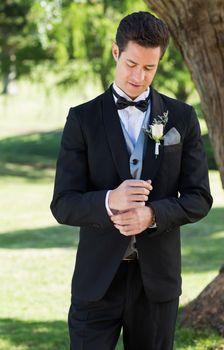Handsome groom adjusting sleeve in garden