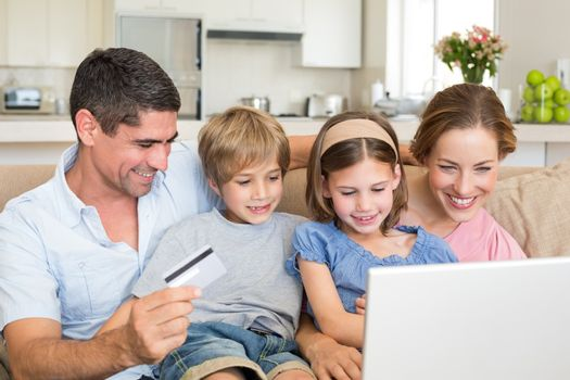 Happy family of four shopping online in house
