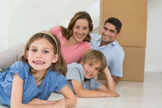 Portrait of happy children and parents lying on floor in their new house