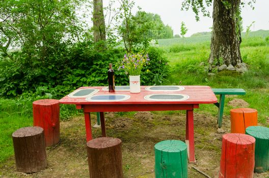garden yard stands large wooden table with bunch of flowers in vase around the colorful painted stumps