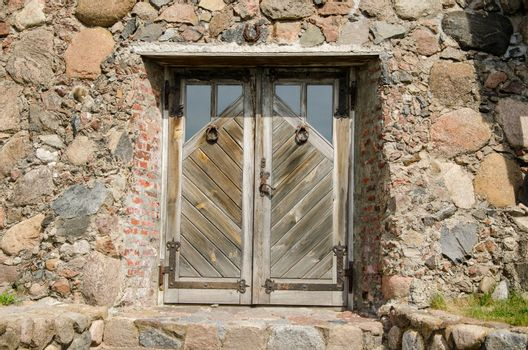 horseshoe  hanging over stone wall building old wooden entrance door