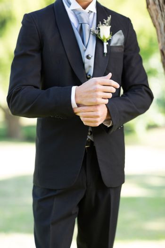 Sophisticated groom adjusting sleeve in garden