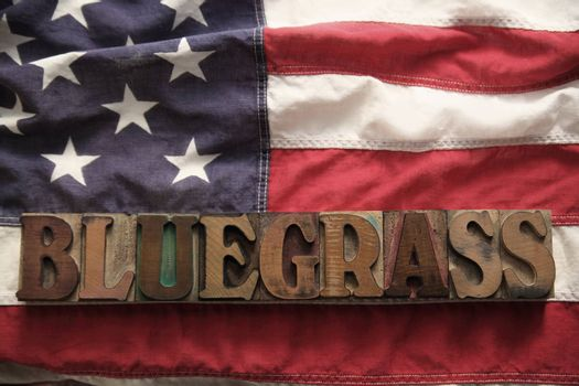 an American flag with the word bluegrass in old wood type