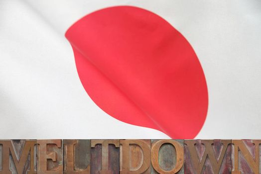 the word meltdown in old wood type on a Japanese flag