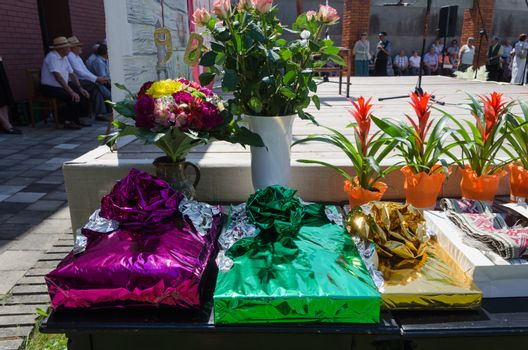 gift in glossy paper and flower roses bouquets and pots on the table city festival event outdoor