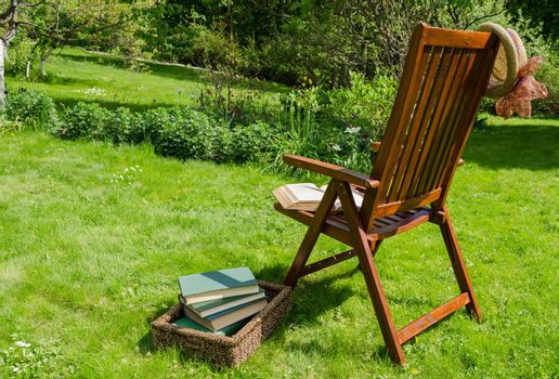 wooden relax chair, books in basket and hat in garden yard in summer day.