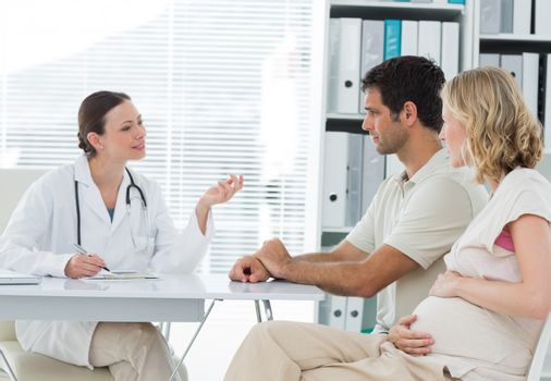 Dynaecologist discussing with expectant couple
