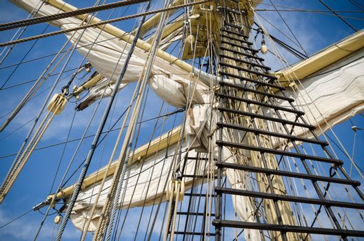 Sails and tackles of a sailing vessel on a background of the sky