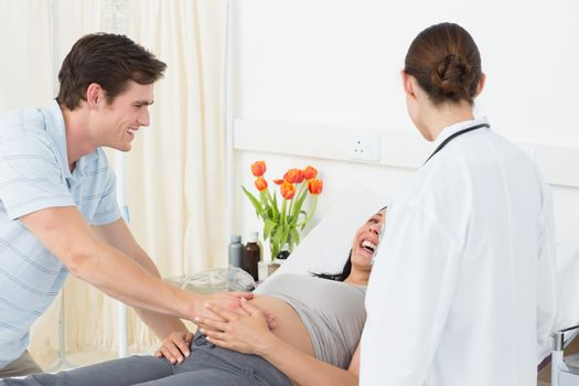 Doctor with happy expectant couple