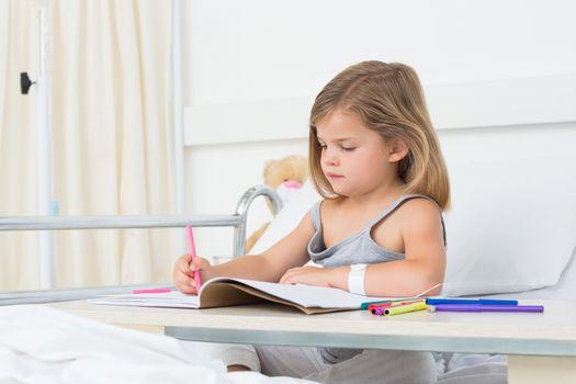 Girl coloring book in hospital