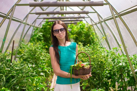 young woman holding a basket of greenery and onion in greenhouse