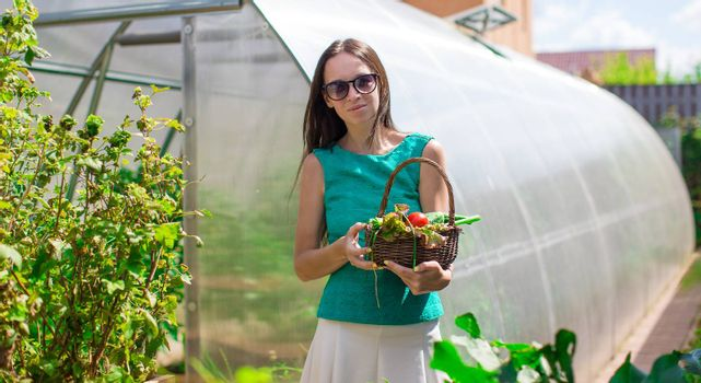 Young woman standing near her greenhouse