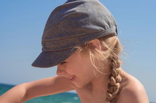 Adorable little girl in denim cap on the beach