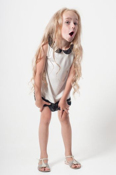 Little girl in white dress fooling around in studio