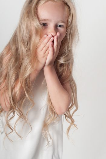 Little girl in white dress covers her mouth with her palms