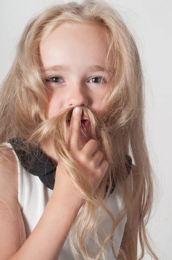 Little girl with long hair fooling around in studio