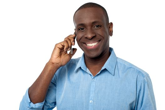 Happy african guy attending a phone call