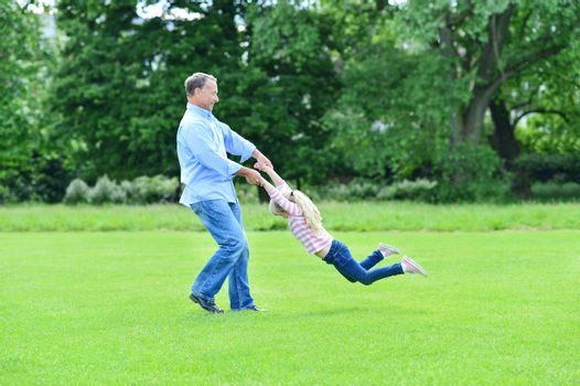 Playful father and daughter having fun in garden