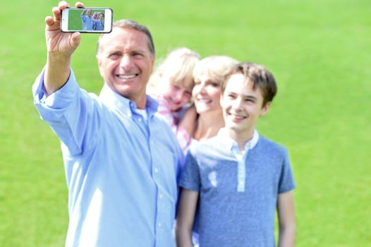 Father clicking family selfie, outdoors.