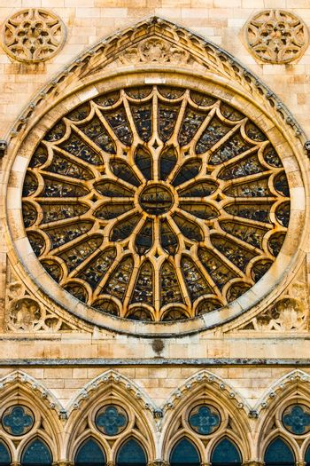 View of the entrance rose window, stained glasses and lancet arch shapes in the gothic cathedral of Leon, Spain