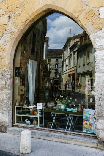 Street refelected from a window display taken inthe city of Perigueux Frech region of perigord
