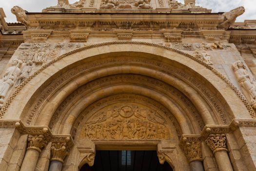 wide view of romanesque arhivolts and carved tympanum in the main entrance door of the San Isidoro Collegiate church in Leon, Spain
