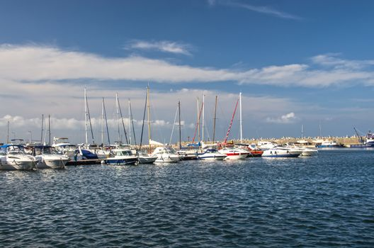 Sailboat and yacht anchored in a harbor.