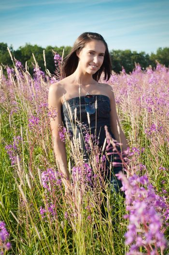Beautiful young girl on the flowers field
