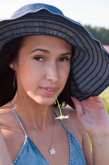 Woman in denim hat with chamomile in mouth