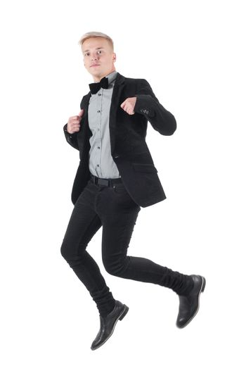 Handsome man in jacket and bow-tie jumping, isolated