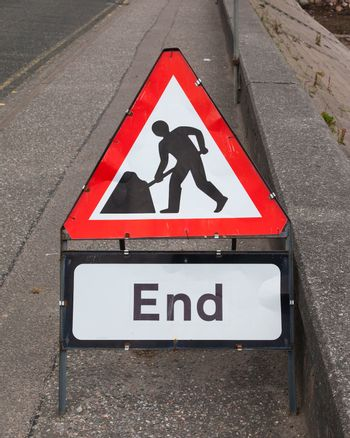 Triangular construction sign standing on footpath