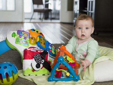 Baby sitting on floor with colorful toys looking at viewer