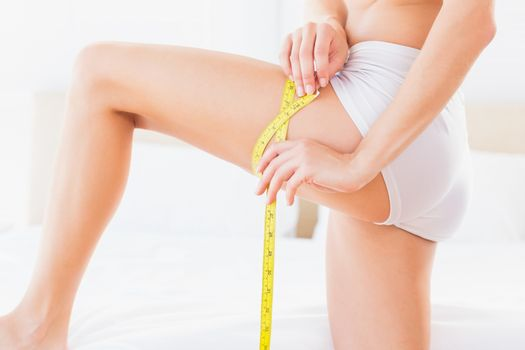 Thin woman measuring her thigh