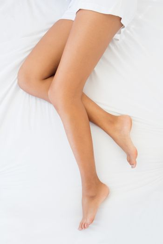 Slim womans legs lying on bed