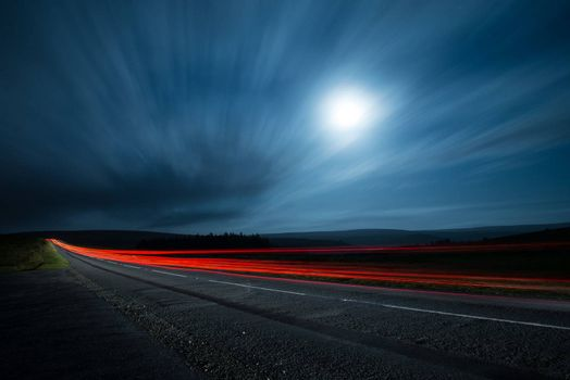 Blur light in night shoot of fast driving car with blurred clouds over full super moon and road