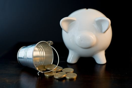 white piggy bank isolated on black background with coins
