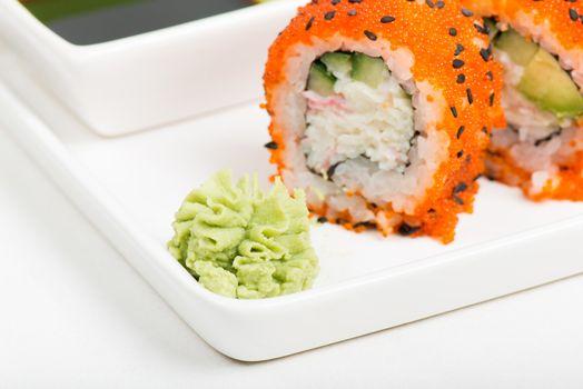 Macro shot of wasabi with sushi rolls on background