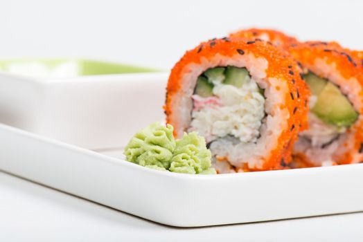 Macro shot of wasabi with sushi rolls on back
