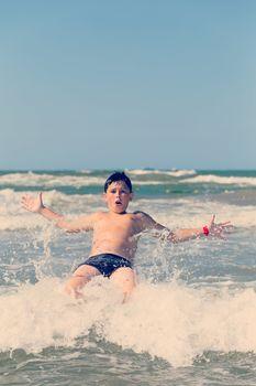 Happy boy running and jumping at shallow sea water