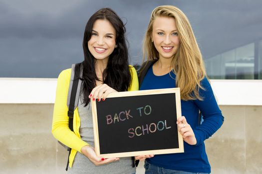 Two beautiful teenage students holding a chalkboard with the slogan Back to School