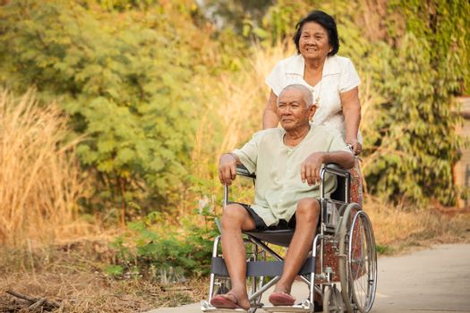 Asian senior woman pushing her disabled hasband on wheelchair