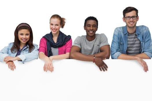 Portrait of happy young friends with blank board